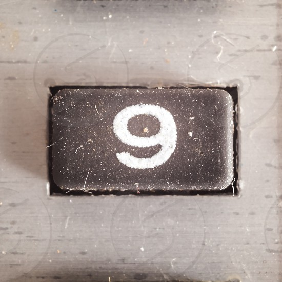 Old dirty and dusty rubberized button with written number on it part of an old calculator.  photo