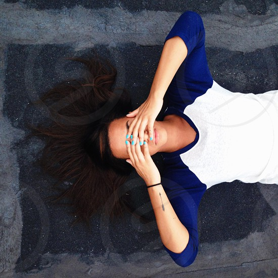 woman in blue and white rascal crew neck shirt lying on grey concrete floor photo