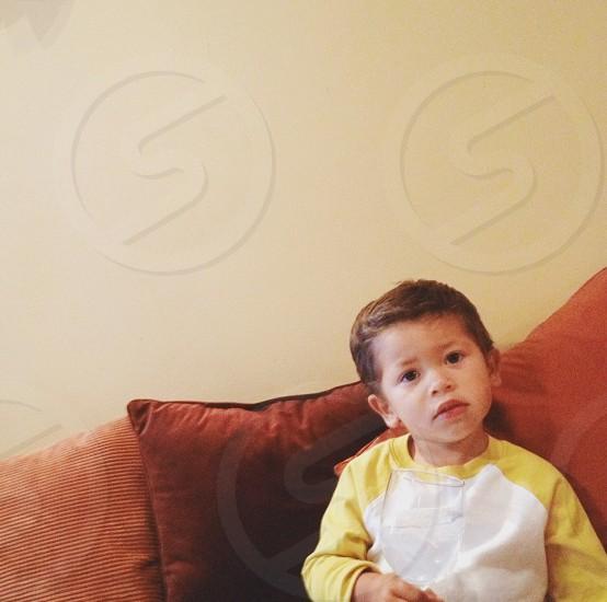 boy sitting near brown throw pillow photo