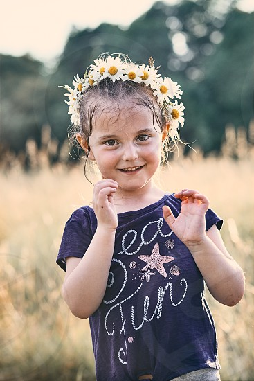 Little girl wearing a coronet of wild flowers on her head. Candid people real moments authentic situations photo