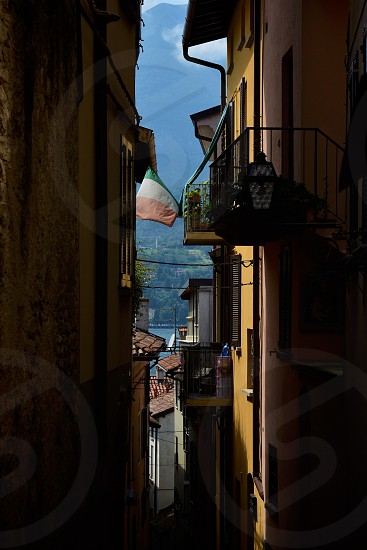 Italian flag flies in a small alleyway in a village along the shores of Lake Como Italy photo
