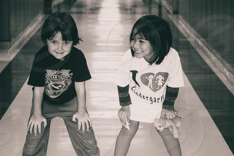 Black and white photo of a little boy and little girl smiling for the camera photo