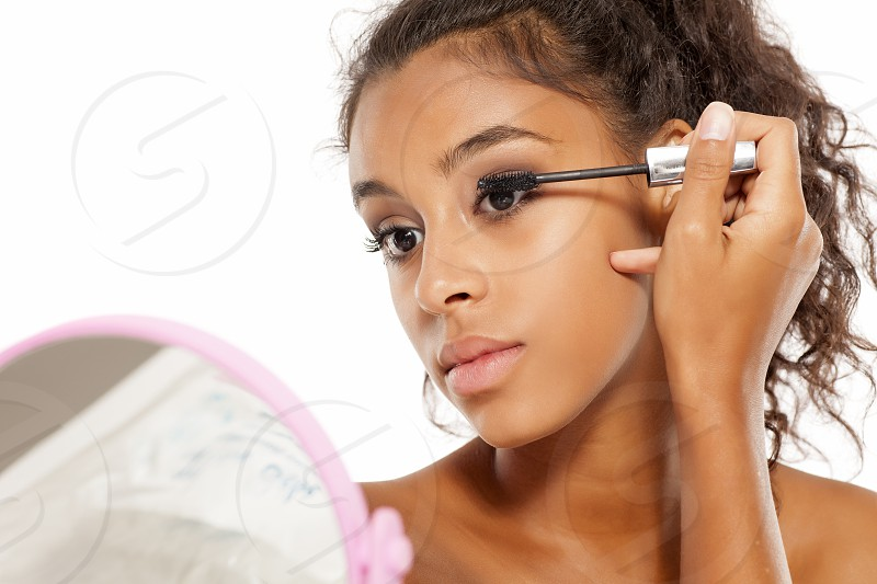 a young dark skinned woman applying a mascara to her eyelashes photo