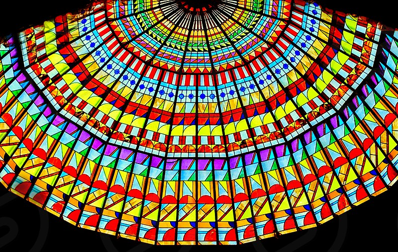 Looking up at light through a vividly colored glass ceiling. photo