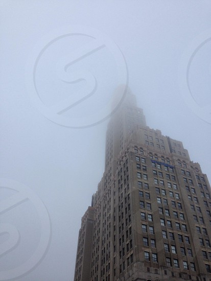 low-angle photography of gray concrete building surrounded by fog during daytime photo
