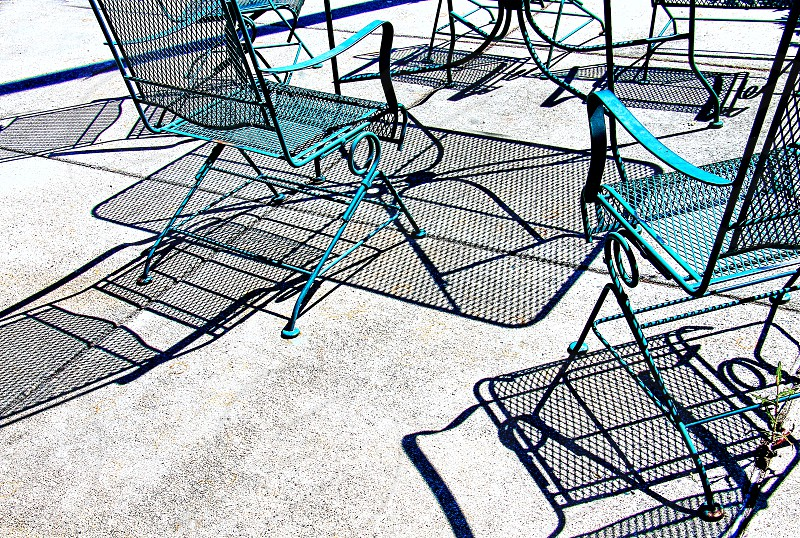 Metal patio chairs throw abstract shadows on the ground. photo