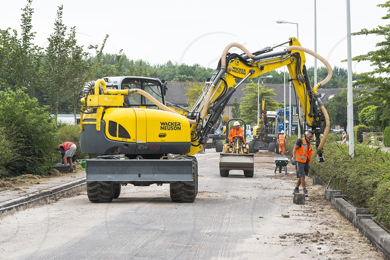 HellevoetlsuisNetherlands-12-July-2018:construction workers are busy in renewing the road in the villageone in a white the streets have to get new asphalt and will be closed for several weeks photo