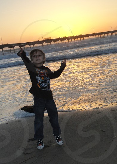boy in black sweater with prints and blue denim jeans photo