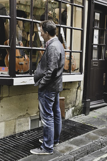 Man window shopping in guitar shop window photo