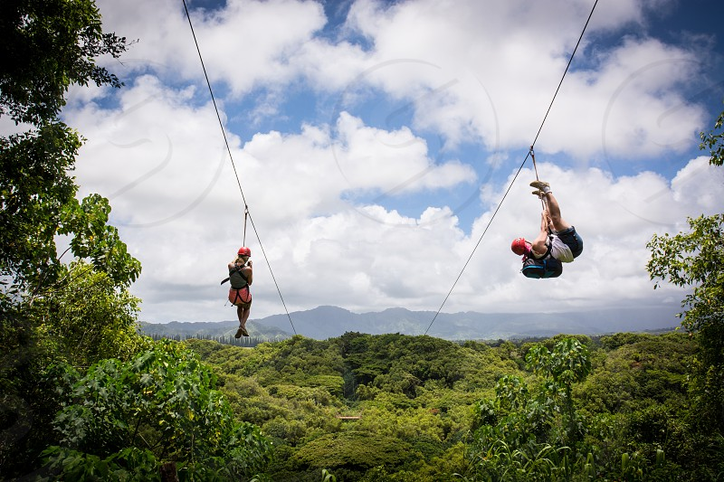 zip line zip lining white clouds green plants trees blue mountains people red orang helmets fun adventure epic vista photo
