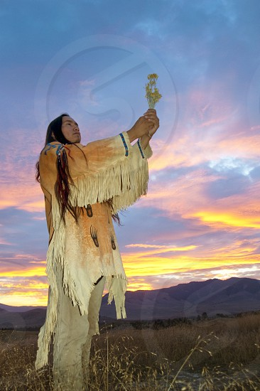 Traditional Native American  man makes an offering of plant medicine to the Great Spirit during a glorious sunset over the Northern Plains photo