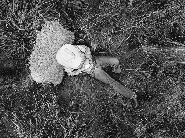 man in cowboy hat sitting on grass leaning on haystack in high angle greyscale photography photo