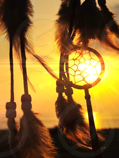 indian dream catcher with feathers silhouetted against sun photo