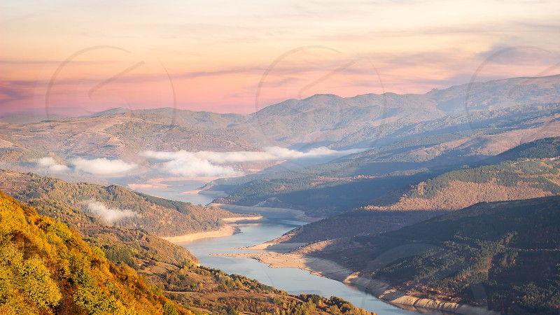 Autumn scene from viewpoint Goat rock with soft view of meandering lake Zavoj during misty purple sunrise photo