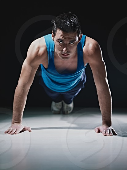 guy; man; sport; working out; fitness; push-ups; push ups; 20s; 30s; active; adult; aerobics; athlete; athletic; beautiful; black background; black; background; brunette; caucasian; concentration; copy space; determination; effort; endurance; exercise; exercising; fit; floor; gym; health; healthy; indoors; lifestyle; looking at camera; muscle; one person; people; pushups; sportswear; strength; strong; sweat; tanktop; training; wellbeing; wellness; white; workout; young photo