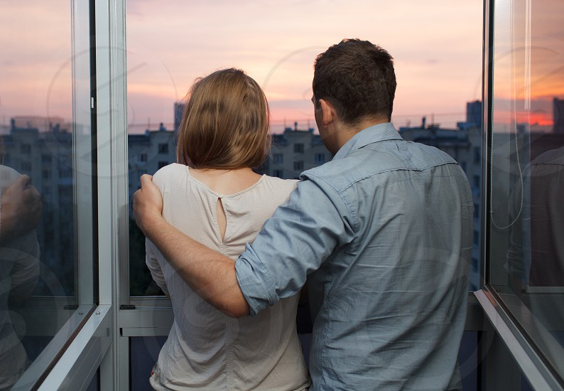 Young couple on the balcony at a high floor looking at city during sunset photo