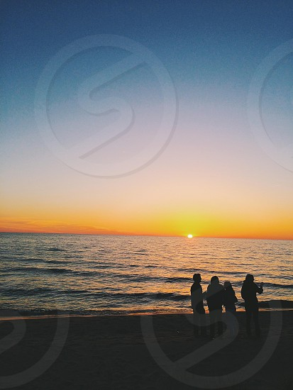 people on beach side overlooking sea and sunset photo