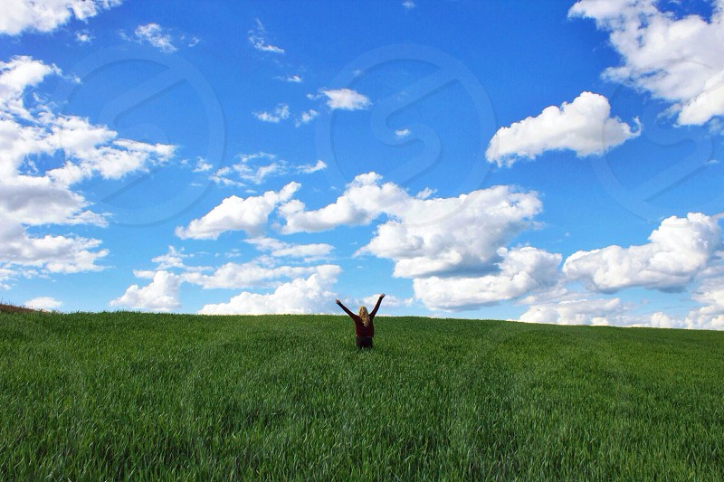 woman in black sweater arms up blue sky in field photo