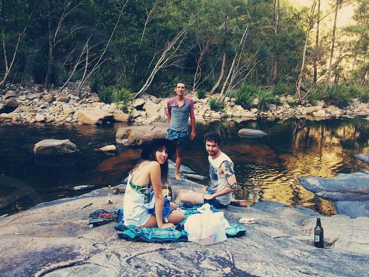 peope on large rock along riverside  photo
