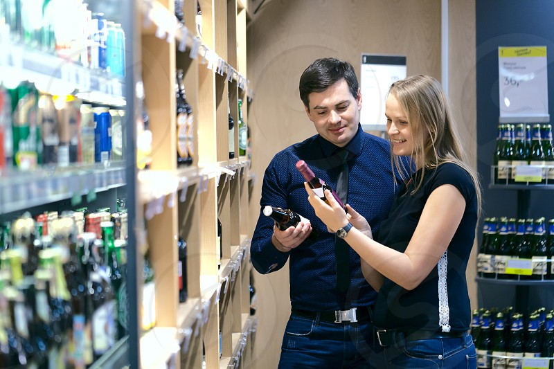 Attractive couple standing choosing wine in a bottle store looking at two bottles off the shelves full of merchandise photo