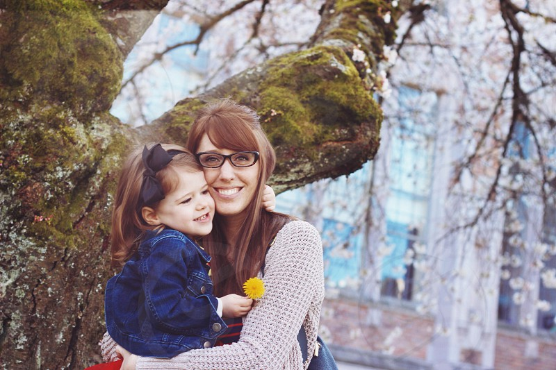 woman and child standing by a moss covered tree photo