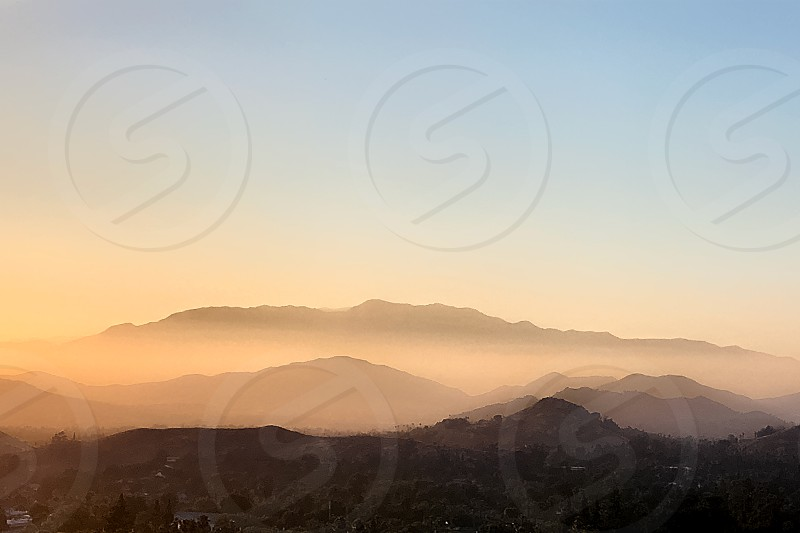 Hills are silhouetted against a golden yellow and orange sunset. photo