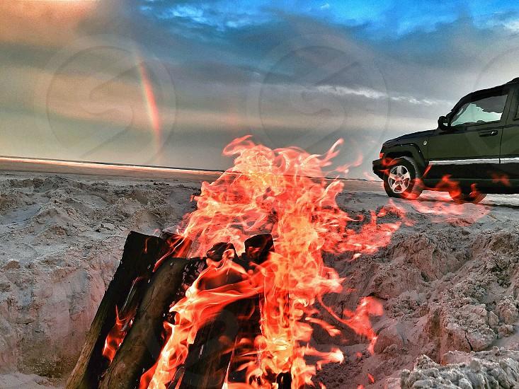 Having a bonfire on the beach with a rainbow and my Jeep.  photo