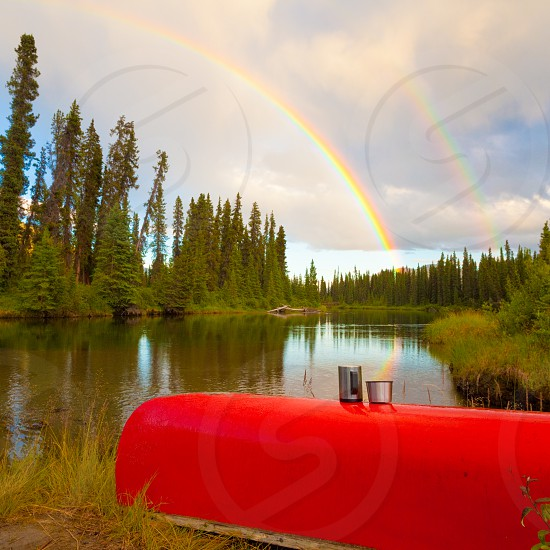 Overturned canoe with coffee mugs under bright rainbow on shore of Big Salmon River Yukon Territory Canada photo