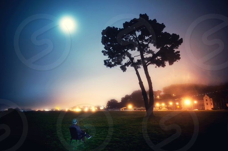 person sitting in lawn chair under moonlit sky  photo