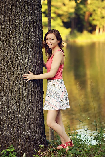 girl in pink tank top holding large tree trunk photo