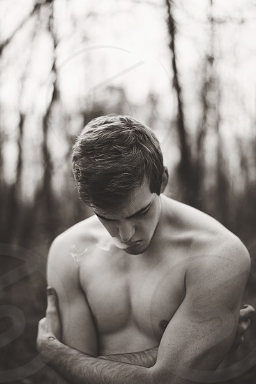 Man exhaling smoke alone in the woods. photo