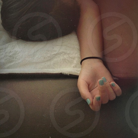 woman with teal nail polish lying on bed photo