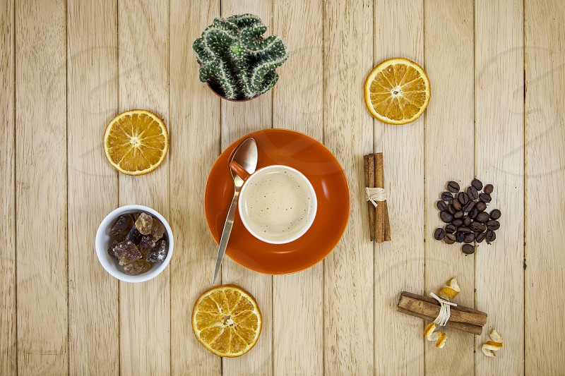 white ceramic mug on brown round plate beside sliced oranges and brown nuts photo