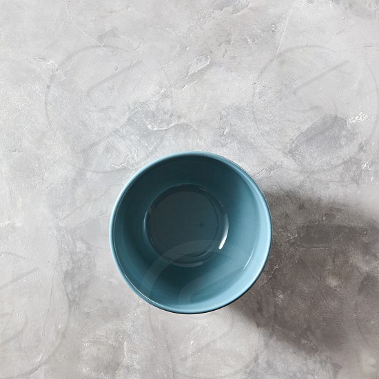 Blue hand crafted chinese bowl blue color on gray stone background with copy space. Flat lay photo