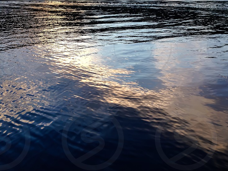 Water reflecting sky. Water color ripples reflection  photo