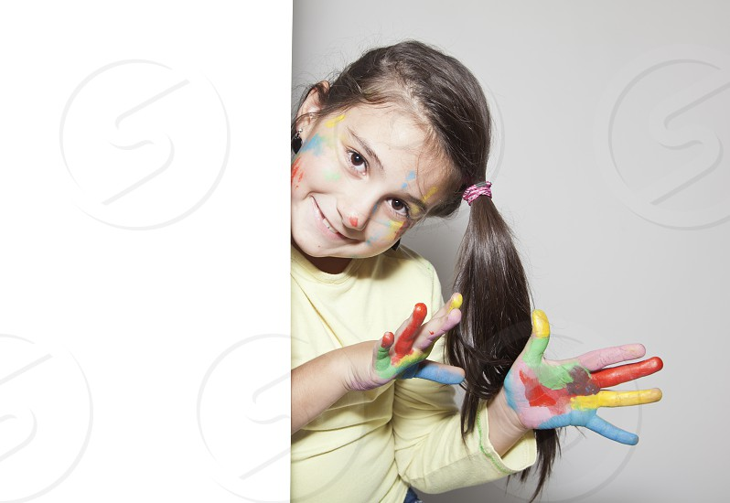Happy 7 years old girl with painted hands behind white blank paper photo