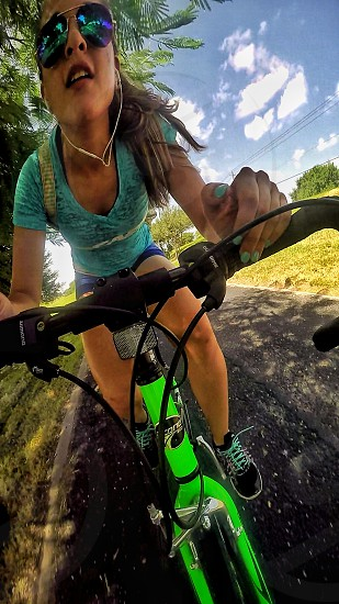 fish eye lens photo of woman wearing blue shirt shorts and sunglasses biking on road surrounded with grass and trees during daytime photo