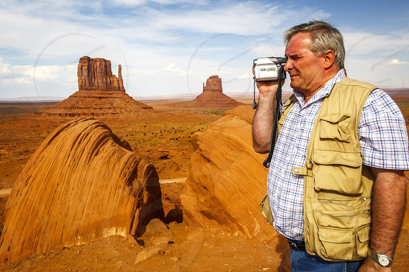 Man using old style video camera at tourist attraction Monument Valley Tribal Park in Arizona photo