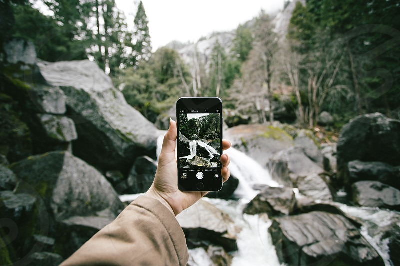 person holding an iphone out to take a picture of a white waterfall running over grey rocks in front of green pine tree forest photo