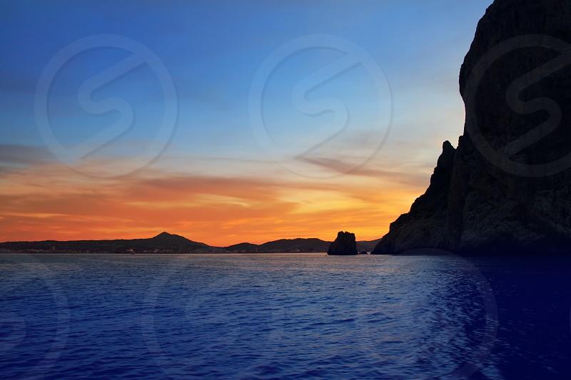 Cape San Antonio Javea Xabia sunset view from sea Mediterranean backlight Alicante Spain photo