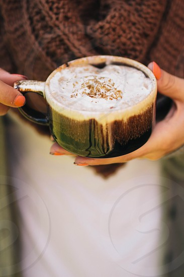 person holding a green ceramic cup of cappuccino photo