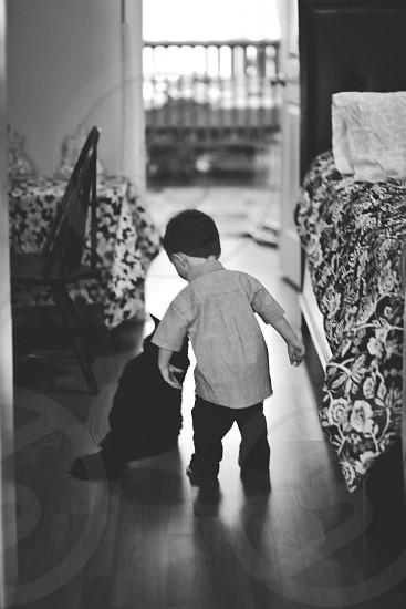 boy standing beside cat on parquet floor photo