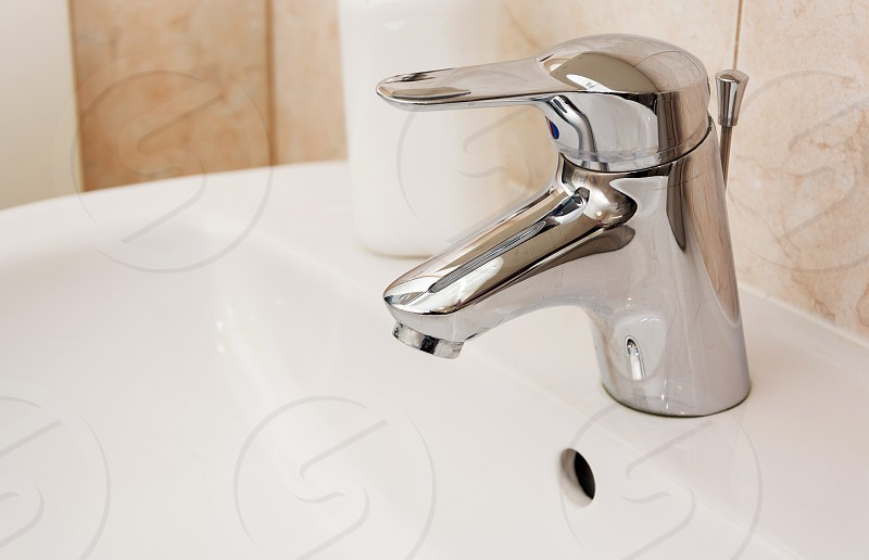 close up view of a faucet in a white sink photo