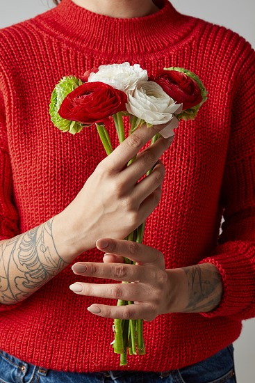 girl with a tattoo on her hands in a red knitted sweater holds a bouquet of flowers. a happy Valentine's day photo