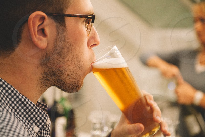 man in white and black checked dress shirt drinking beer near woman in gray long sleeve shirt photo