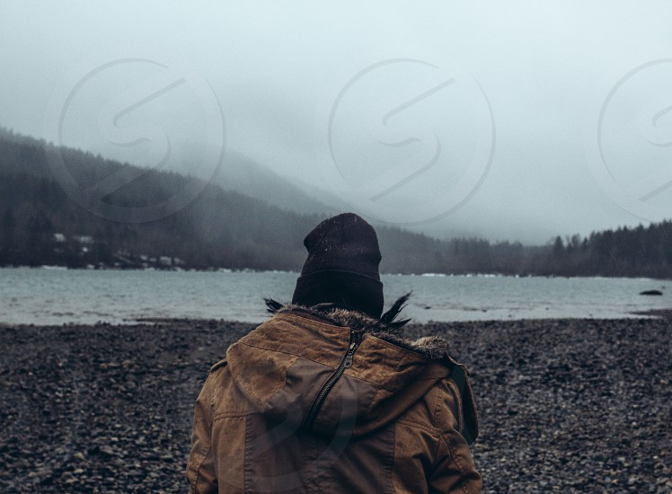 person in brown hoodie and black beanie standing near body of water and mountain during daytime photo
