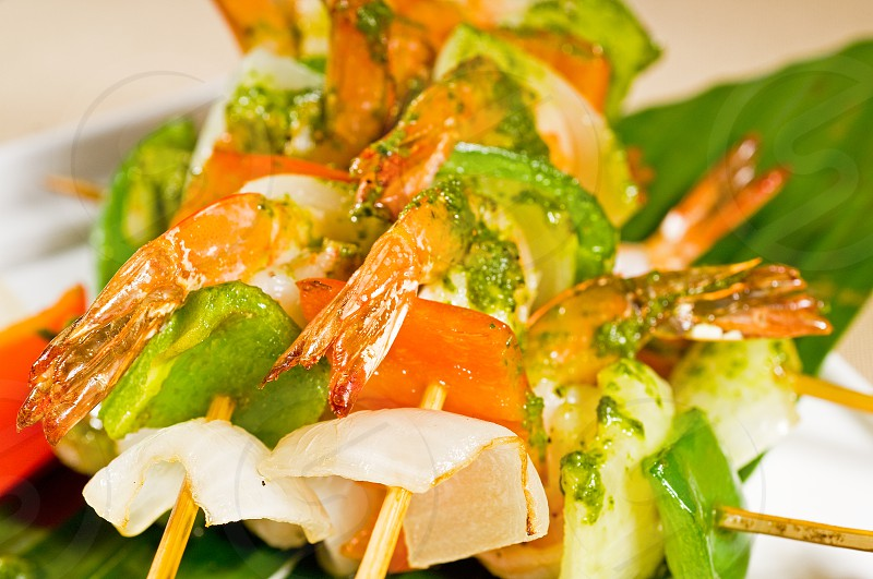 fresh and colorfull grilled shrimps and vegetables skewers on a palm leaf thai style photo
