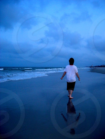 Man walking along a beach at night with his reflection in the wet sand photo
