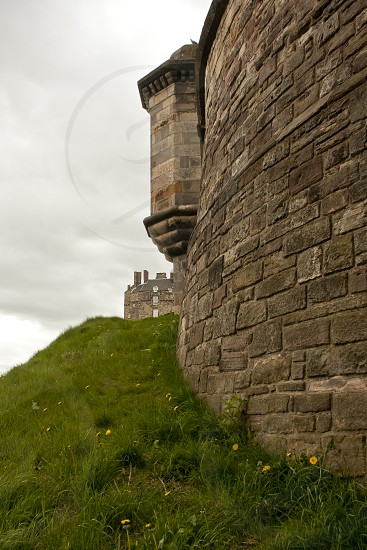 Edinburgh Castle wall with Edinburgh Castle in the background on a stormy day.  Taken from Wynd Steps photo