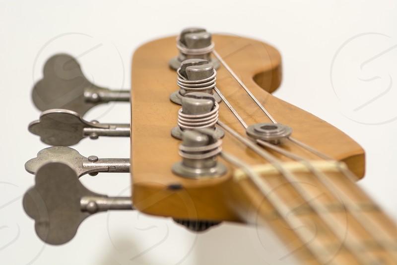 bass guitar music musician strings frets tuners machine heads nut neck headstock tuning keys wood beige white instrument equipment photo